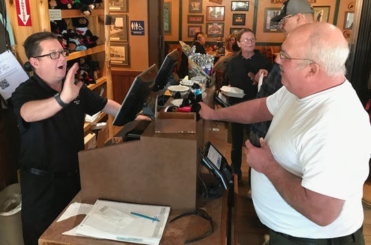 Shasta County Sheriff Tom Bosenko, right, pays for breakfast at the Black Bear Diner in Redding with restaurant general manager Tim Thurman behind the register in October 2019. Bosenko lost PG&E power during the recent outage but had a small generator to keep his refrigerator and freezer running at his home outside Redding.