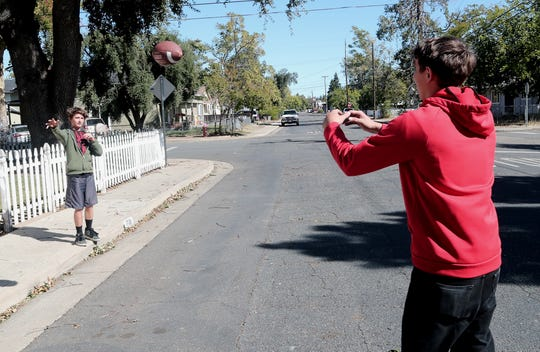 Anderson Middle School student Branden Conklin, left, tosses a football on his street with brother Tyler Conklin, 21, on Thursday, Oct. 10, 2019, during the PG&E outage. Many North State schoolchildren went outside to ride their bikes, scooters and skateboards instead of playing video games because of the power shortage.