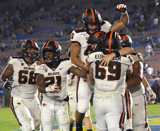 Oct 5, 2019; Pasadena, CA, USA; Oregon State Beavers offensive lineman Brandon Kipper (68), running back Artavis Pierce (21), offensive lineman Nous Keobounnam (69) and tight end Ralph Taufa'asau (45) swarm quarterback Jake Luton (6) after he runs  in for a touchdown in the fourth quarter against the UCLA Bruins at the Rose Bowl. Mandatory Credit: Jayne Kamin-Oncea-USA TODAY Sports