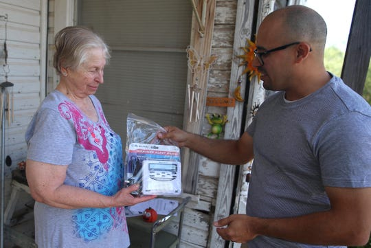 Yvonne Keele, left, receives a weather radio from Eric Martinez as he makes his deliveries for Meals for the Elderly on Thursday, Oct. 10, 2019.