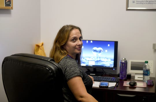 Kelly McColligan, 40, a COAT member and Safe Station supervisor, poses from her desk at the Recovery Resource Center in Salisbury, Maryland, on Oct 2, 2019. The mother, in recovery herself and clean for over 9 years, works to help those dealing with addiction find resources to approach recovery.