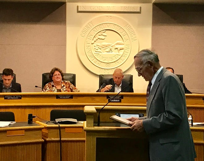 Dr. H. Lynn Moore pauses for a minute and looks over the resolution he received from the Board of Supervisors on Oct. 9, 2019, before speaking. The resolution honors Moore's 60 years of service to Augusta County.