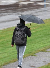 An SCSU student walks through the rain Thursday, Oct. 10, 2019, near Husky Stadium.