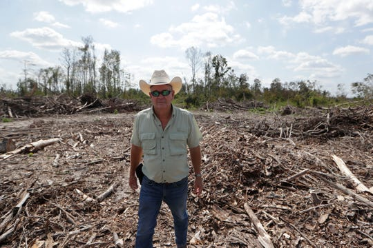 Mack Glass, a farmer in Marianna, Florida, stands in front one of the larger piles of fallen trees and debris that have been collected from his property. Hurricane Michael devastated a majority of Glass' timber farms in Oct. 2018.