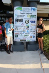 Overall race winners Josh Negron, left, and Chenae Jackson show off their hardware post-race at Indian River State College's Pruitt Campus.