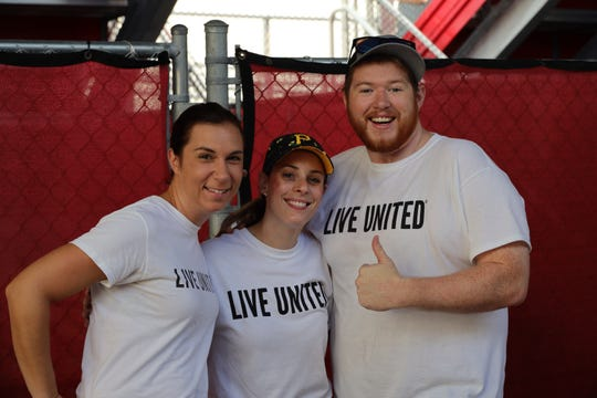 Elizabeth Ullian, left, Caitlin Puppo and Ben Sidorski get ready to help at the Day of Caring Kickoff Breakfast at Billy Livings Field on Oct. 5, 2019.