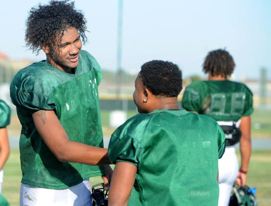 Devin Aupiu, left,  talks with Malik Sherrod during Pacific's practice on Tuesday.