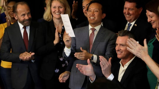 California Gov. Gavin Newsom applauds, lower right, after signing Assembly Bill 1482 Tuesday in Oakland. The law will cap rent increases at 5% each year plus inflation.