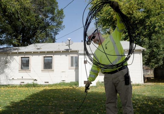 Jay Brown with Southern California Edison rolls up wires that were cut to a house Thursday at the Fillmore Fish Hatchery after some of them came down in high winds. Downed power lines were among a number of problems Ventura County faced as Santa Ana winds surged.
