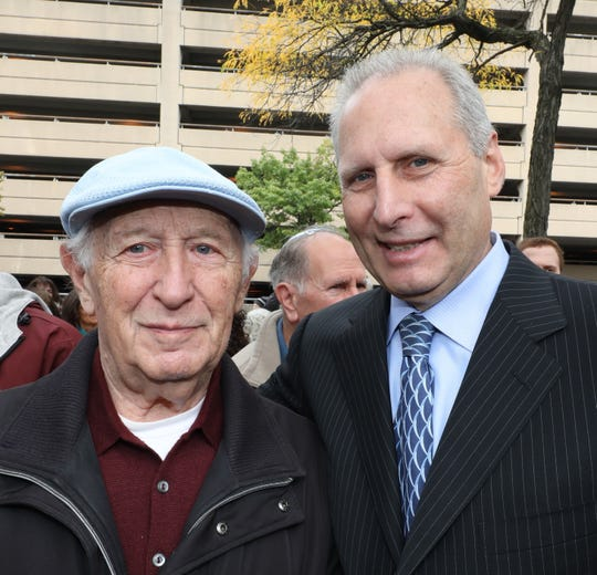 Holocaust survivor Jerry Kaidanow and his son Joseph are pictured on the sidewalk in front of the Holocaust Garden of Remembrance in White Plains, during an interfaith vigil Oct. 10, 2019. Joseph Kaidanow is the chairman of the board for the Holocaust & Human Rights Education Center.
