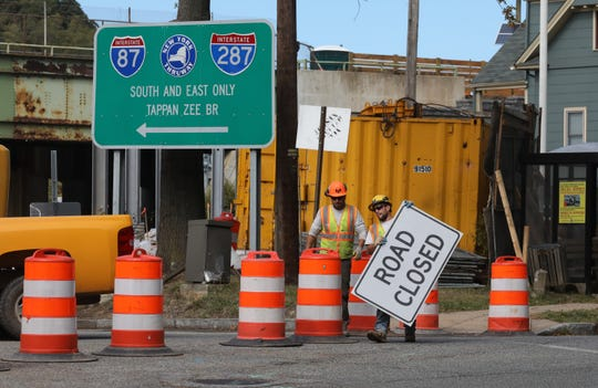 A construction worker puts a road closed sign up to the South Broadway entrance to the New York State Thruway in Nyack Oct. 10, 2019.