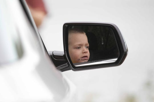 3-year-old Grayson Maloney looks out the window of his mother Mallory Read's car as rescue workers recover a body in the Chesapeake & Delaware Canal Thursday morning. Read, a mother of four, lives in nearby St. Georges and has been driving along the canal every day since the Lindsey family lost three boys, two brothers and a cousin, after their car plunged into the C&D Canal. The search has been ongoing to find Ethan Lindsey, 6.