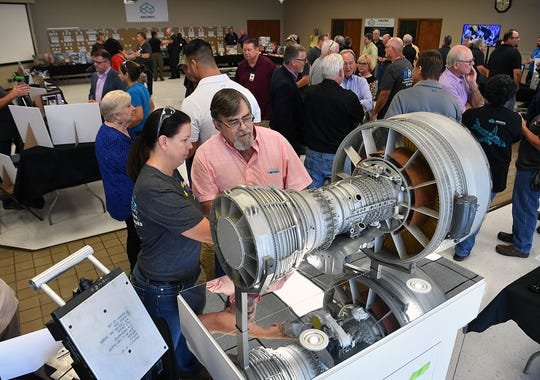 Arconic Quality Engineer Michelle Kelsey and Paul Stratton look over a model of a CF-6 jet engine that the company makes parts for. Arconic held an open house and mark their 40th anniversary this week. Stratton retired after 32 years with Arconic.