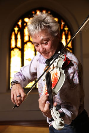 """Laura Schumann is a professional violinist, a conductor, a published composer and arranger, and, of course, a horse whisperer. """"I like to say I'm so far out of the box, there is no box,"""" she said."""