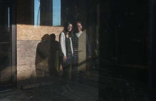 Reflected in the window of the former Montgomery Ward building on Fourth Street in Zanesville, Brad Pauquette and his wife Melissa hope to transform the building into the School of Kingdom Writers.
