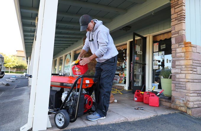 Cliff Dunn, owner of Pawsarotti's pet store, runs a generator in order to keep a freezer full of raw pet food cold during a power outage in Santa Rosa, Calif., Oct. 9, 2019.