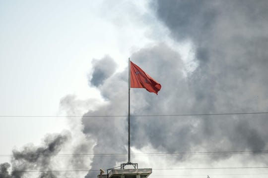 A picture taken in Akcakale at the Turkish border with Syria on Oct. 10, 2019, shows the Turkish flag as smokes rises from the Syrian town of Tal Abyad after a mortar landed in Akcakale.