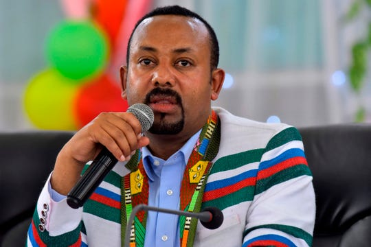 Ethiopian Prime Minister Abiy Ahmed, wearing a white coat bearing the traditional Kafficho colours of red, green and blue,  address the crowd in Bonga, the main town in Kaffa province, some 449km south west of the capital Addis Ababa, on September 15, 2019.