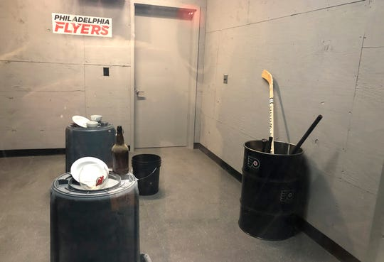 """Hockey sticks sit in a barrel, right, in the """"Rage Room"""" before the Philadelphia Flyers' NHL hockey game against the New Jersey Devils on Wednesday, Oct. 9, 2019, in Philadelphia. Grab a helmet and baseball bat and step up to the plate - Flyers fans can take a swing for fun or just to take out frustrations on bottles, dishes or even a fishbowl stamped with the visitor's logo. (AP Photo/Dan Gelston) ORG XMIT: RPDG321"""
