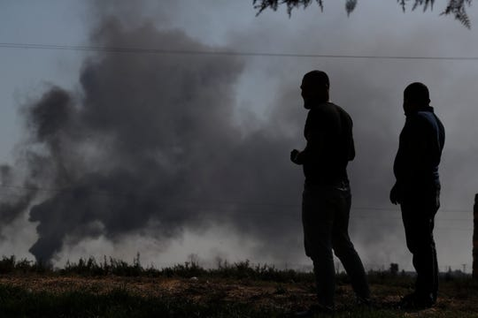 People watch from the Turkish side of the border between Turkey and Syria, in Akcakale, Sanliurfa province, southeastern Turkey, as smoke billows from targets inside Syria during bombardment by Turkish forces on Oct. 10, 2019.