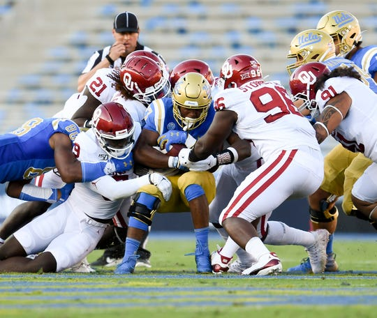 Oklahoma's defense swarms to tackle UCLA running back Joshua Kelley during their game on Sept. 14, 2019 at the Rose Bowl.