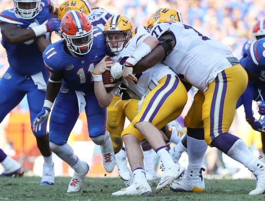 LSU quarterback Joe Burrow is talked by Florida defenders during the second quarter of their 2108 game at Ben Hill Griffin Stadium.