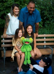 """Jaana and Sam Woodbury, from Irvine, Calif., and their daughters Salia, 10, right, and Kya, 6, with """"Sesame Street"""" muppet Karli and puppeteer Haley Jenkins in New York. The Woodburys are in recovery, and Salia is featured with Karli in a """"Sesame Street"""" segment about addiction."""