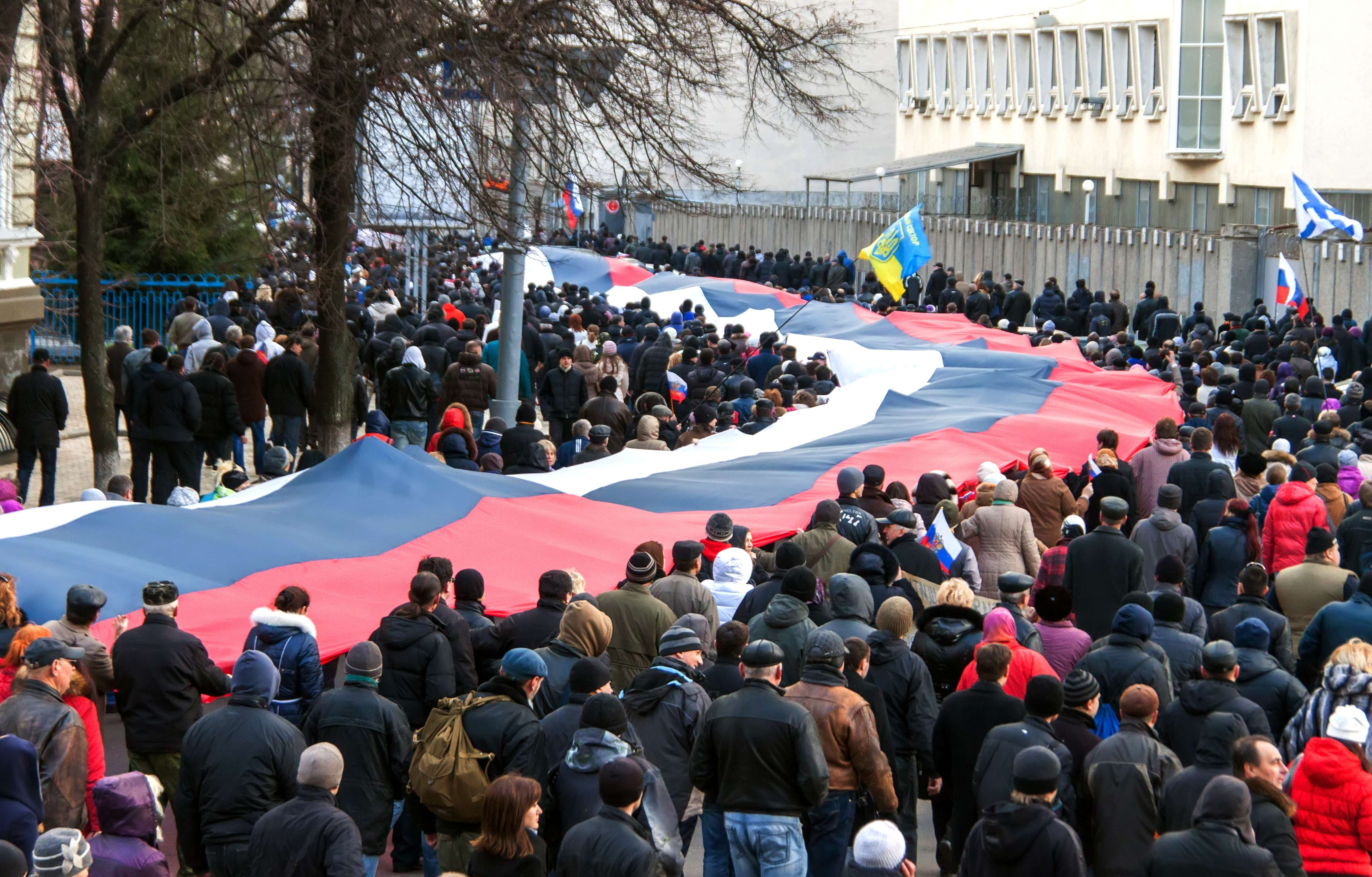 """Pro-Russian supporters carry a huge Russian flag during a rally in Kharkiv, eastern Ukraine, some 40 km from the Russian frontier, on March 16, 2014. 6,000 protesters held a """"meeting-referendum"""" to ask for more independence and reclaim the """"sovereignty"""" of the Russian language, on the day Crimea voted to join Russian rule and break away from Ukraine."""