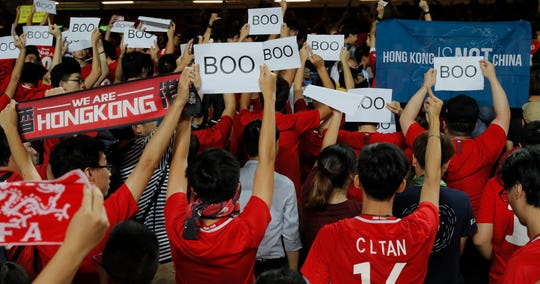 "Hong Kong soccer fans turn their back and boo the Chinese national anthem as they chant ""Hong Kong is not China"" during the FIFA World Cup qualification  match between Hong Kong and Iran in Hong Kong."