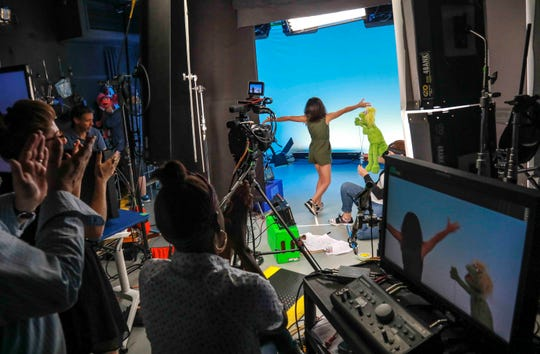 """Production members clap for Salia Woodbury, 10, from Irvine, Calif., on the set with """"Sesame Street"""" muppet Karli and puppeteer Haley Jenkins during an Aug. 6, 2019, taping about parental addiction. Sesame Workshop is addressing the issue of addiction. Data show 5.7 million children under 11 live in households with a parent with substance use disorder. Salia's parents are in recovery after struggling with addiction, and she shares her experience with the show's Karli—whose muppet character has a mom who is also in recovery."""