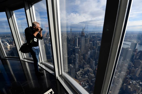 A member of the media snaps a picture of the New York City skyline from the 102nd floor of the Empire State Building.
