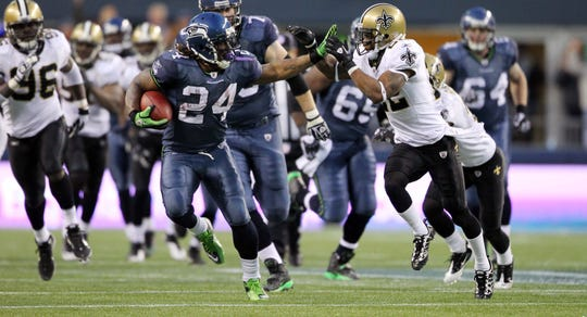 "Marshawn Lynch stiff arms the Saints' Tracy Porter en route to the famous ""Beast Quake"" touchdown in the2011 wild-card playoff in Seattle."