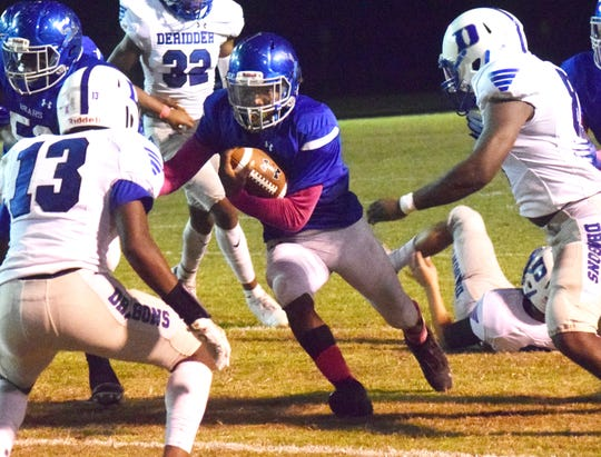 Bolton quarterback Jadarius Welch picks up yards against Deridder High School in District 3-4A play Thursday, Oct. 10, 2019. Deridder won 13-9.