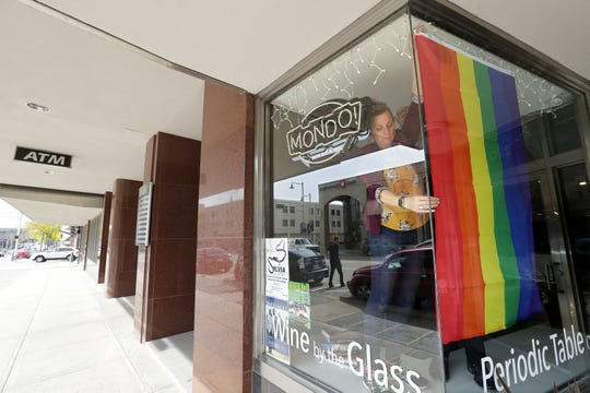 Mondo! Wine Bar & Retail owners Jane and David Oliver display a rainbow flag in support of the LGBTQ community for part of National Coming Out Day on Oct. 11. Appleton is publicly celebrating the day for the first time.