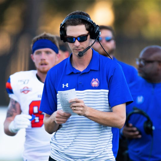 Zach Kittley looks over his play sheet as Houston Baptist plays Texas Wesleyan on Sept. 7 in Houston. Kittley, who grew up Abilene before his family moved away in 1999 when he was 8, is a second-year offensive coordinator and quarterbacks coach for the Huskies.
