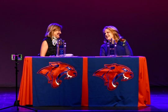 Cooper Hall of Fame inductees Cathy Ashby, left, and Donna Wise laugh on stage of the school's performing arts center after they were inducted into the hall at a homecoming ceremony on Friday, Oct. 11, 2019.