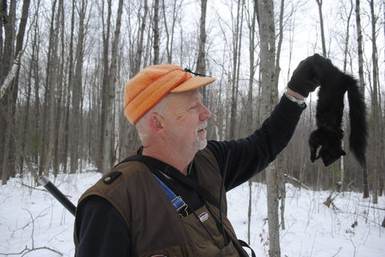 In this 2015 photo, Doug Gilley admires a black squirrel taken during a small game hunt.