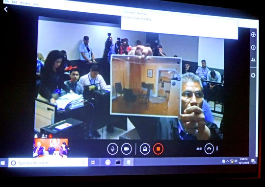 A photograph of the apartment where the body of Haley Anderson was found murdered in March 2018 is held up for the camera in the Nicaraguan courtroom where Orlando Tercero is being tried for Anderson's murder. Witnesses were being questioned via video livestream from Binghamton. Friday, October 11, 2019.