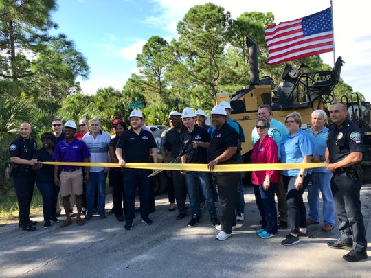 Palm Bay Deputy Mayor Brian Anderson holds a large pair of scissors as city officials line up for a road paving ribbon-cutting ceremony Friday at Firethorn Road and Thunderbird Avenue.