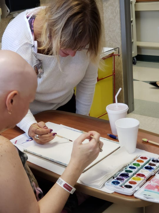 A patient completes a painting as part of Orlando Health's Arts in Medicine program.