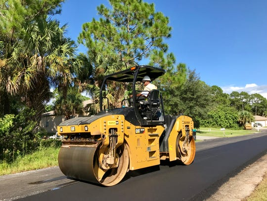 A steamroller rumbles along Firethorn Road on Friday in northwest Palm Bay.