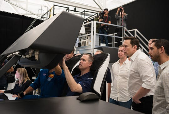 NASA Administrator Jim Bridenstine, center, participates in a Crew Dragon flight simulation with NASA astronauts Doug Hurley and Bob Behnken, while SpaceX CEO Elon Musk looks on.