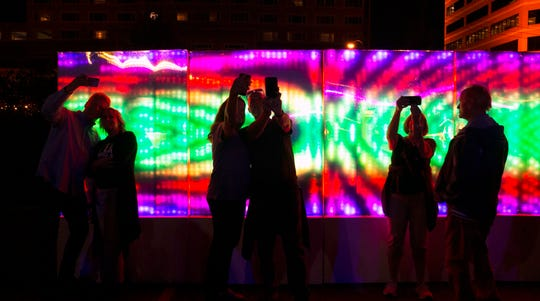 "Blink 2019 goers take selfies at the ""Lumen-Wall 2.0"" by Francisco Cardona and Billy Bryant in downtown Covington."