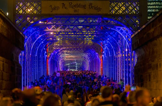 "Hundreds of people crowd the Roebling Suspension Bridge, as lights entitled, ""Rumble"" are projected on the bridge for Blink 2019 Thursday, October 10, 2019. Blink runs until Sunday."