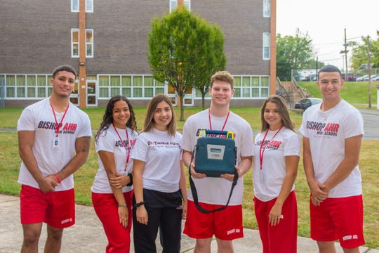 (Left to right): Alejandro Santiago, Melina Roig, LIlibeth Azcona-Parajon, Devlin Stein, Giavanna Brito, Gerard Chiricolo, students at St. Thomas Aquinas High School, pose with an AED purchased through a grant funded by the American Heart Association.