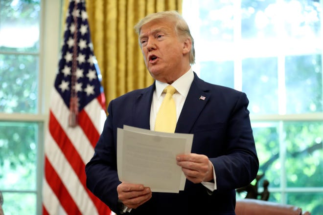 President Donald Trump holds a letter as he meets with Chinese Vice Premier Liu He in the Oval Office of the White House in Washington on Oct. 11.