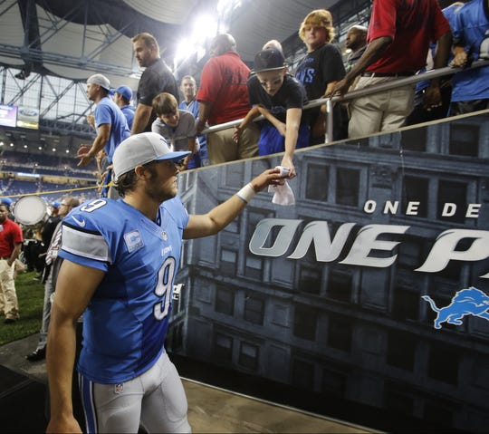 Detroit Lions Matthew Stafford gives a sweatband to a fan as he leaves the field after their 40-32 win over the Chicago Bears in Detroit, Sunday, September 29, 2013. Julian H. Gonzalez /Detroit Free Press