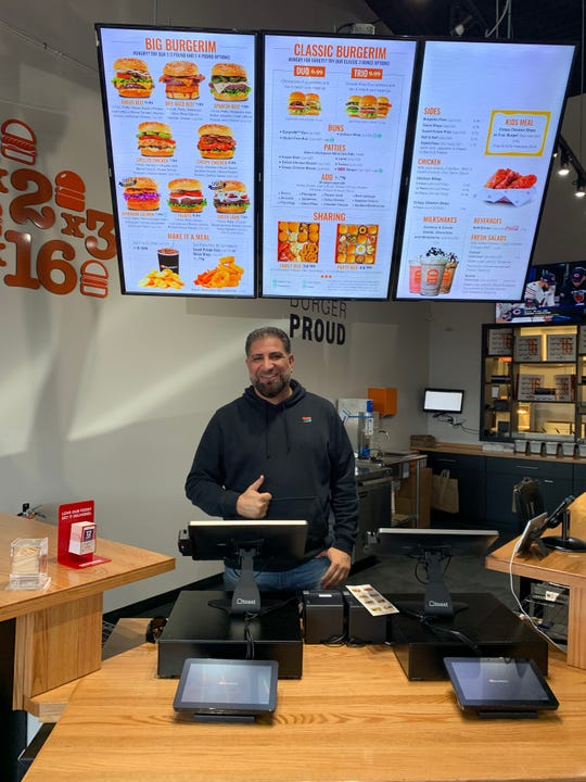 Franchise owner Sam Zahr poses for a photo behind the counter of BurgerIM in Oak Park.