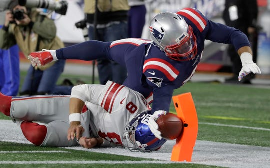 New England Patriots linebacker Kyle Van Noy dives over New York Giants quarterback Daniel Jones to score a touchdown on a fumble recovery in the second half on Thursday.