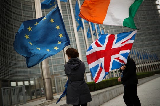 Two anti-Brexit people hold EU, Ireland and Union flags as they wait for the departure of UK Brexit secretary Stephen Barclay during his meeting with European Union chief Brexit negotiator Michel Barnier at the European Commission headquarters in Brussels, Friday, Oct. 11, 2019.